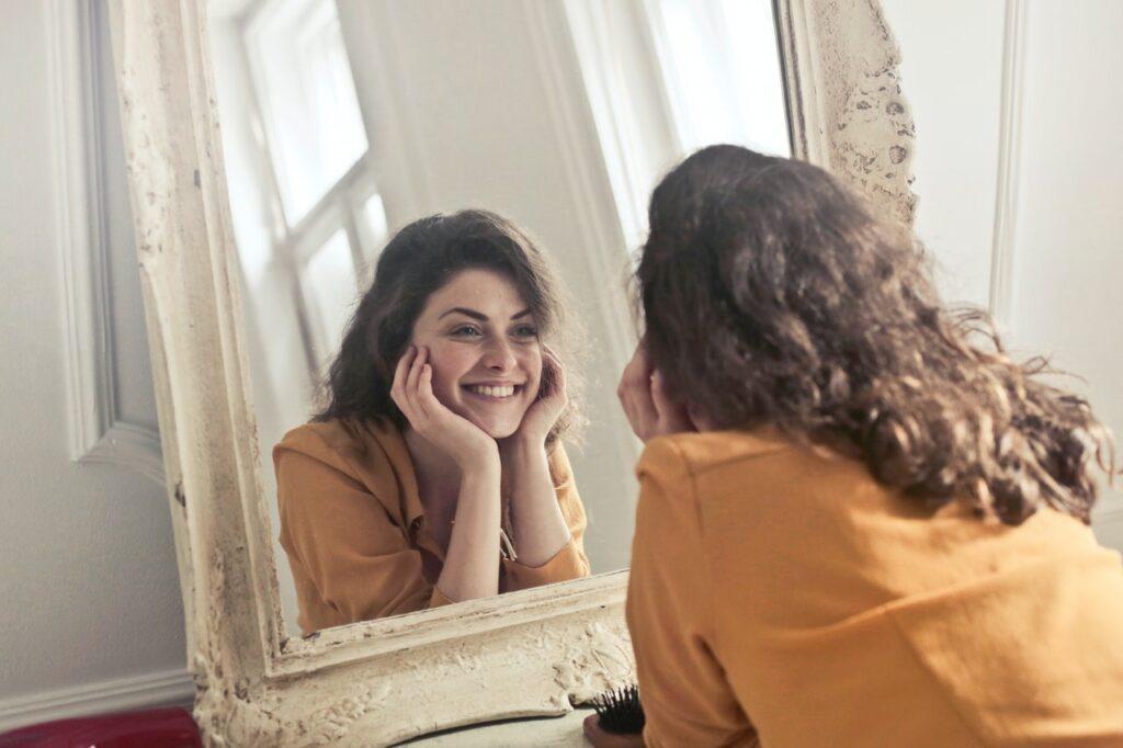 довольное отражение девушки в зеркале