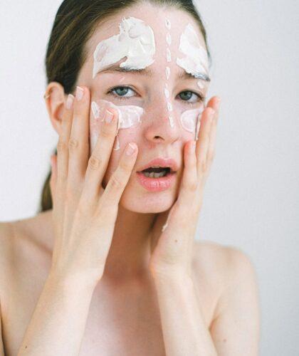 девушка намазывает крем на лицо