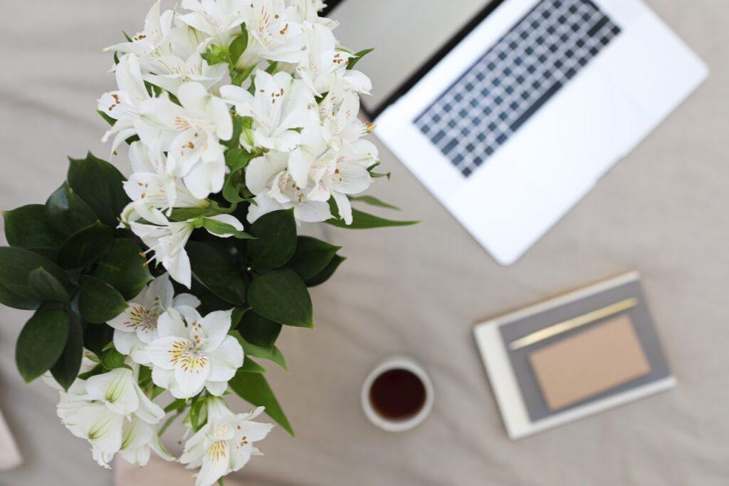 ноутбук и цветы на кровати