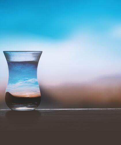 стакан воды на фоне неба