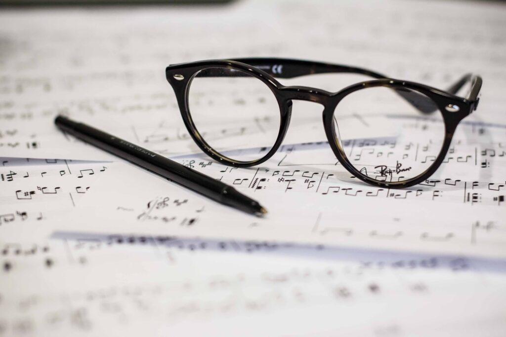 очки и ручка на нотах