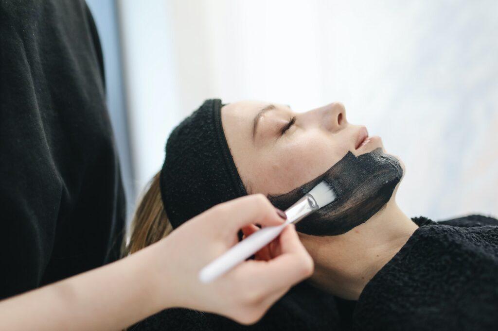 девушке наносят черную маску