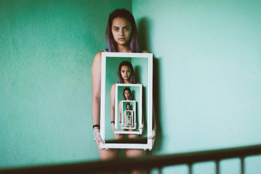 девушка держит портреты себя