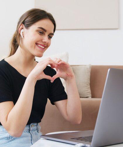 девушка с ноутбуком показывает любовь