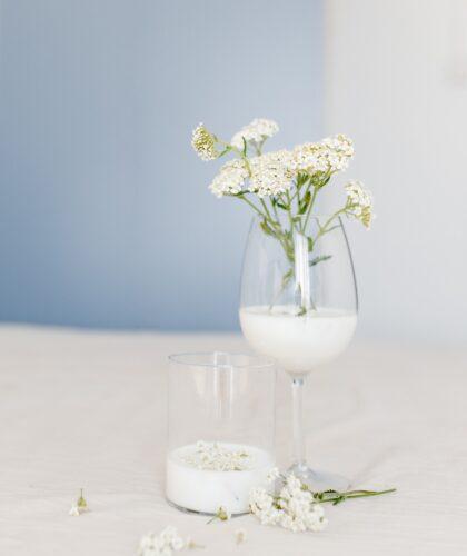 молоко в стакане и бокале и цветы
