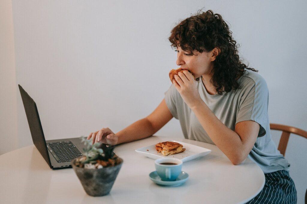 девушка кушает за ноутбуком