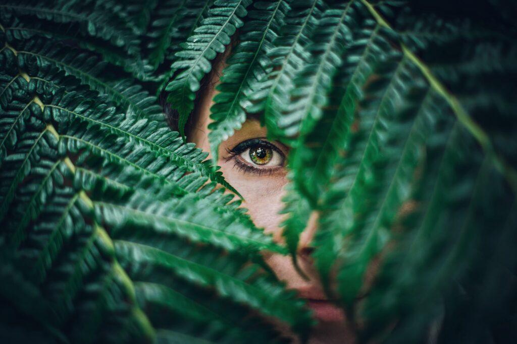 девушка спряталась за листком