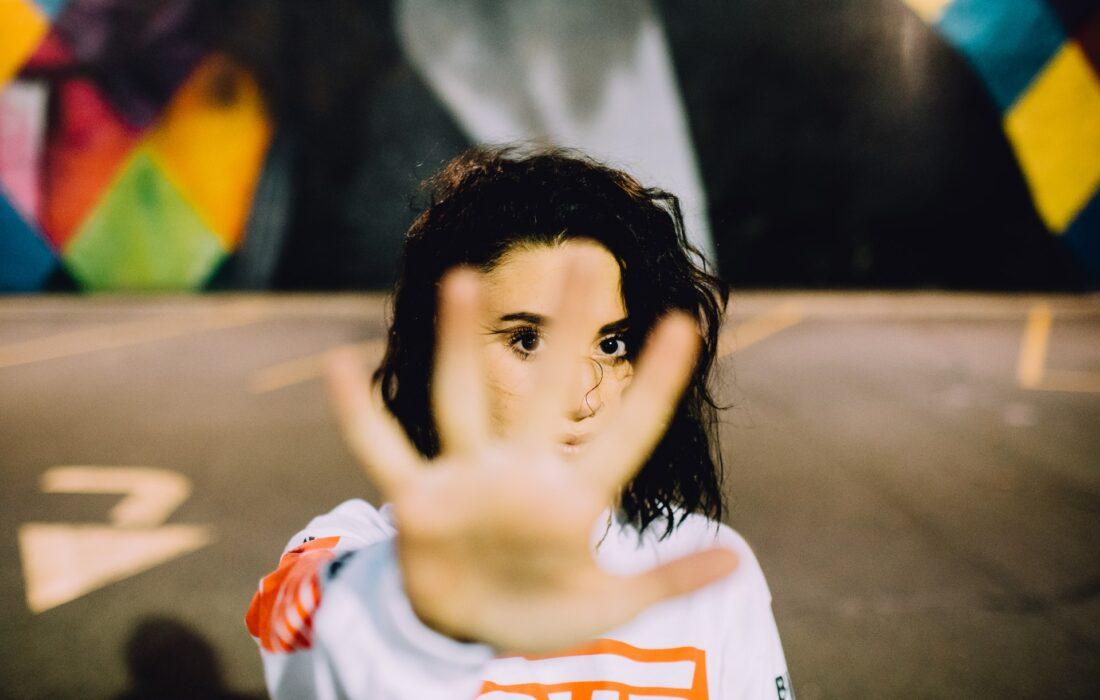 девушка закрывает камеру рукой