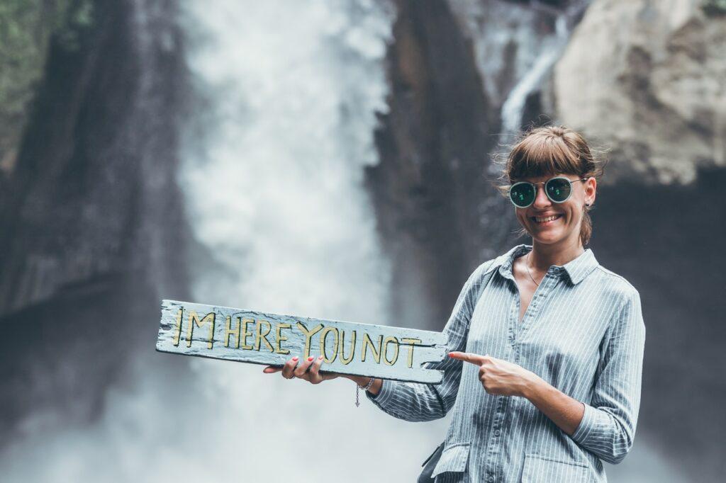 девушка возле водопада с табличкой
