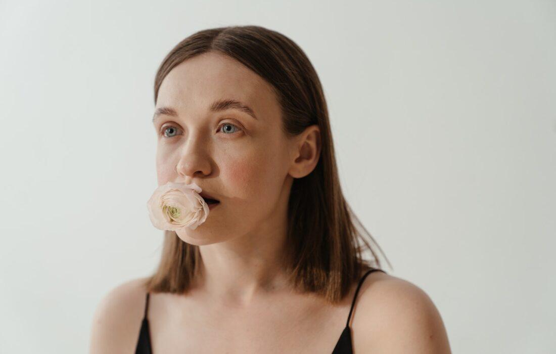 девушка с цветком во рту