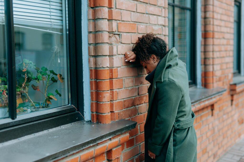 грустная девушка у стены