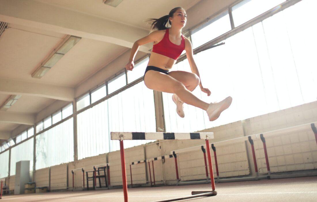 девушка прыгает через барьер