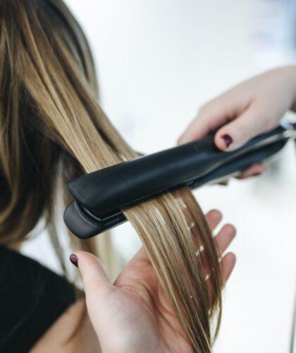 девушке выпрямляют волосы