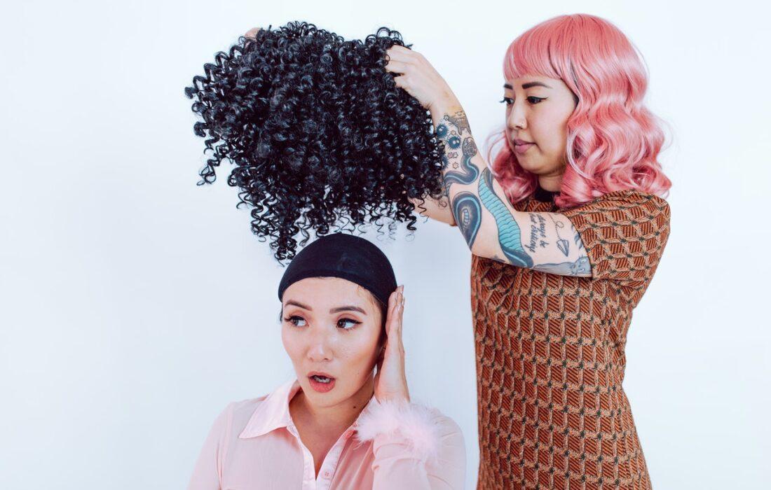 девушка надевает парик на подругу
