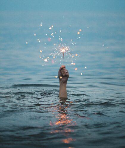 рука с бенгальским огоньком из воды