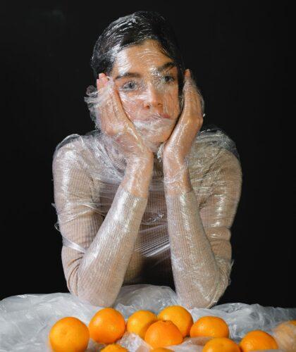 девушка в пленке с апельсинами