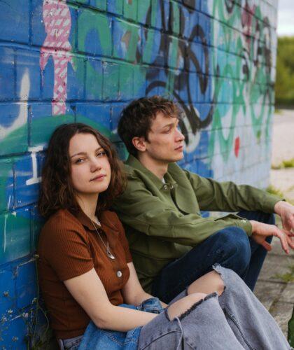 пара сидит у стены