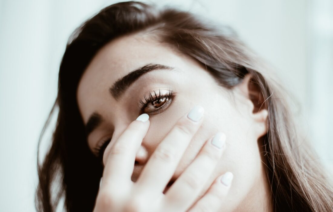 девушка закрывает лицо рукой