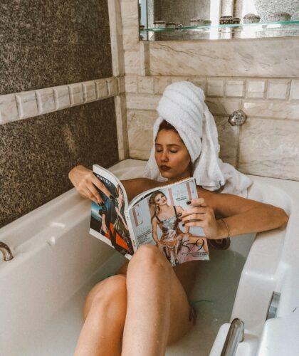 девушка читает в ванной