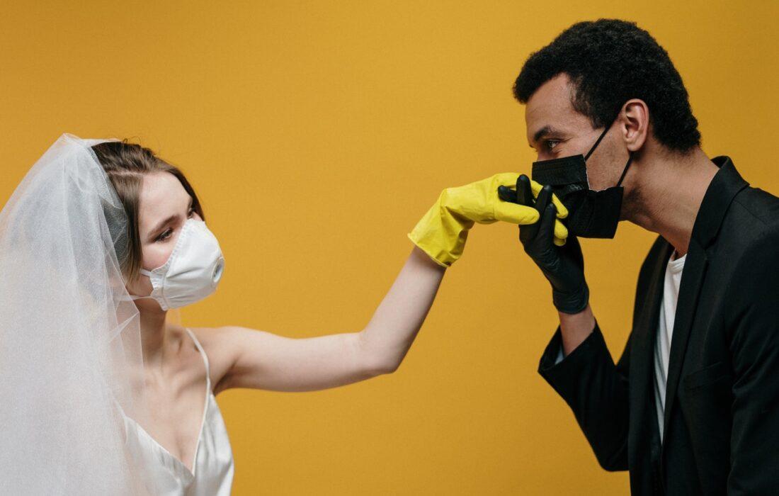 парень целует руку невесте в маске