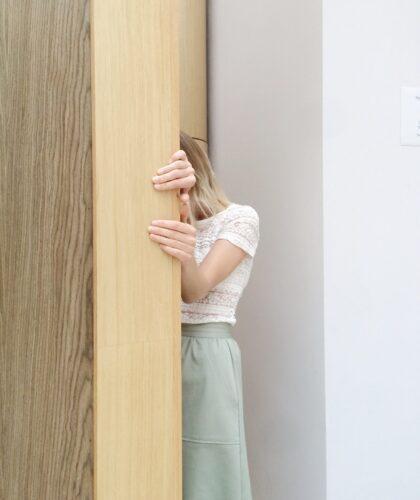 девушка прячется за дверью