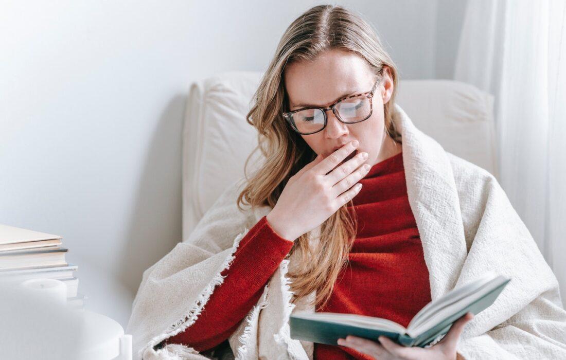 девушка с книгой зевает
