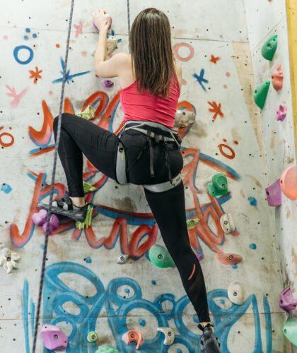 девушка карабкается по стене