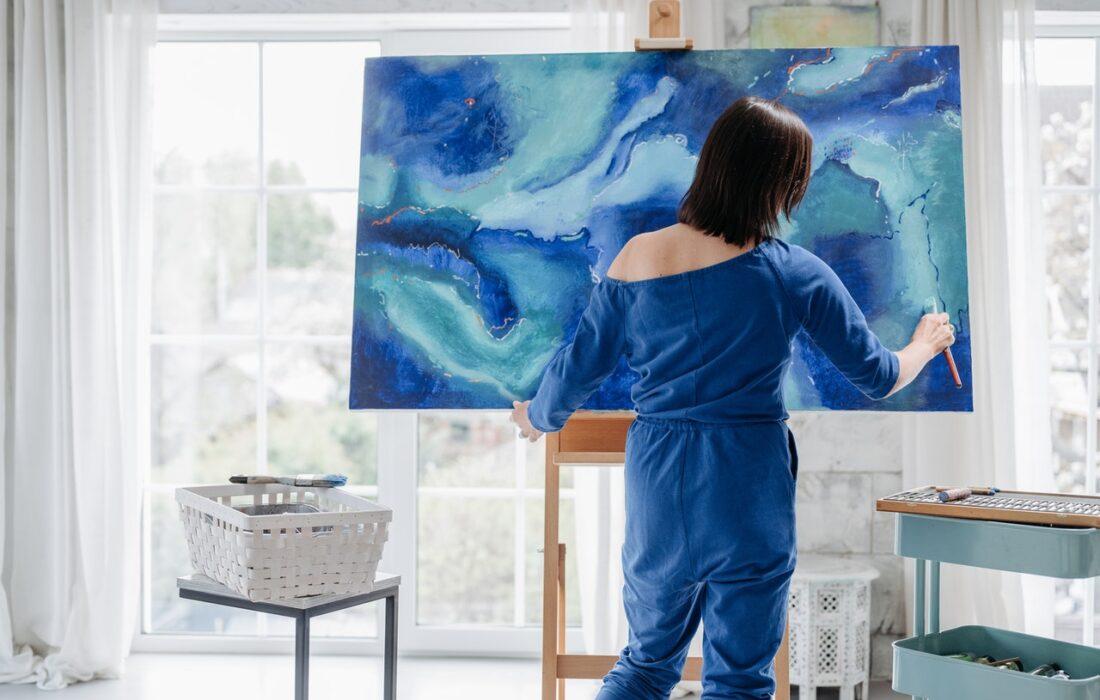 девушка рисует картинку в голубых тонах